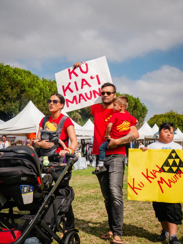 """a family carries """"ku kia'i mauna"""" signs"""